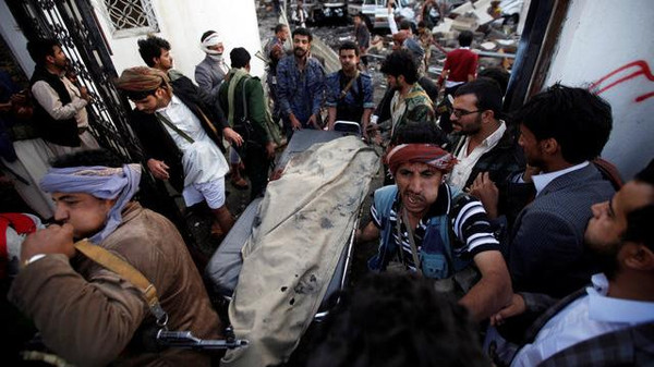 People carry the body of man killed in what witnesses said was an airstrike by Saudi-led coalition aircraft at a hall where a wake was being held, in Sanaa