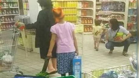 صورة لطفلة ترافق إمراة تستغلها في حمل أكياس ثقيلة